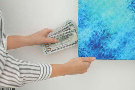 Woman hiding dollar banknotes behind painting indoors, closeup. Money savings 写真素材
