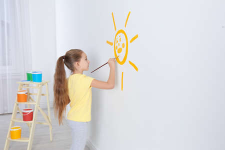 Little child painting sun on white wall indoors