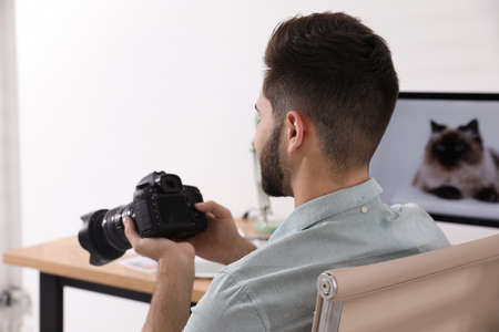 Professional photographer with camera working at table in office