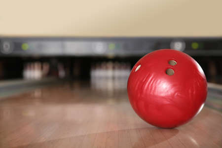 Red ball on bowling lane in club. Space for text