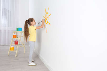 Little child painting sun on white wall indoors, space for text