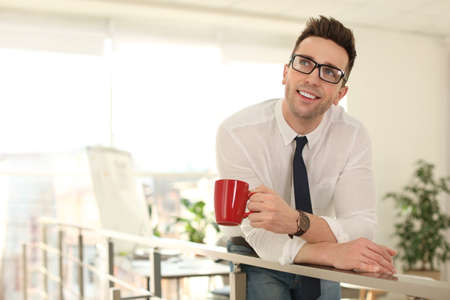 Young businessman with cup of drink relaxing in office during break Zdjęcie Seryjne