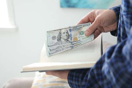Man hiding dollar banknotes in book indoors, closeup.