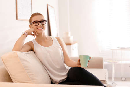 Young woman with cup of drink relaxing on couch in office