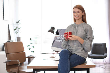 Young woman with cup of drink relaxing in office during break