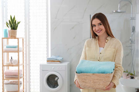 Happy woman with laundry basket in bathroom