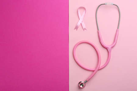 Pink ribbon as breast cancer awareness symbol and stethoscope on color background, flat lay. Space for text