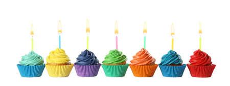 Leckere Geburtstags-Cupcakes mit Kerzen isoliert auf weiß