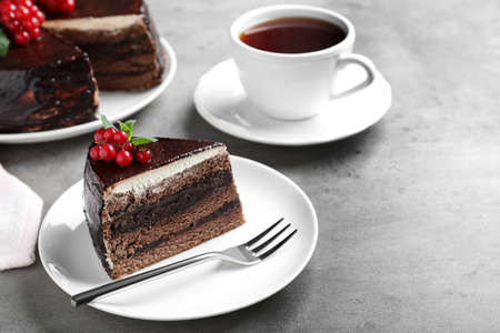 Tasty chocolate cake with berries on grey table Stockfoto