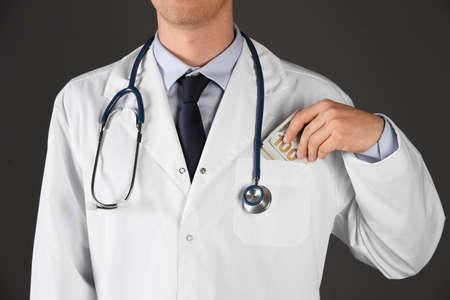 Doctor putting bribe into pocket on black background, closeup. Corruption in medicine