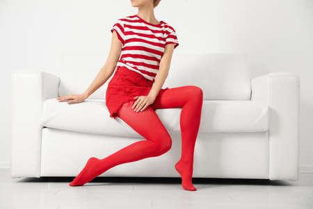 Woman wearing red tights sitting on sofa indoors, closeup Standard-Bild