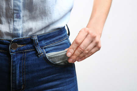 Woman showing empty pocket on light background, closeup