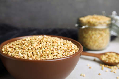Uncooked green buckwheat grains in bowl on table