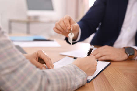 Real estate agent working with client in office, closeup
