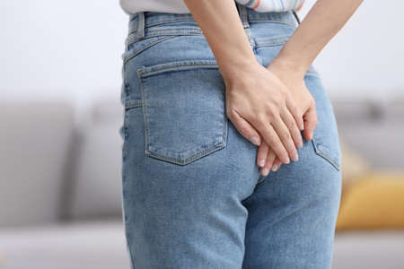 Young woman suffering from hemorrhoid at home, closeup Stockfoto