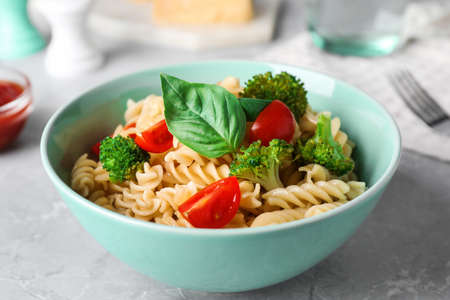 Tasty pasta with broccoli, cherry tomatoes and basil on light grey marble table, closeup