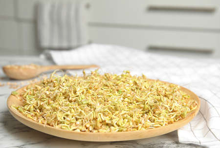 Wooden plate of sprouted green buckwheat on white marble table