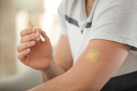 Man with nicotine patch and cigarette, closeup