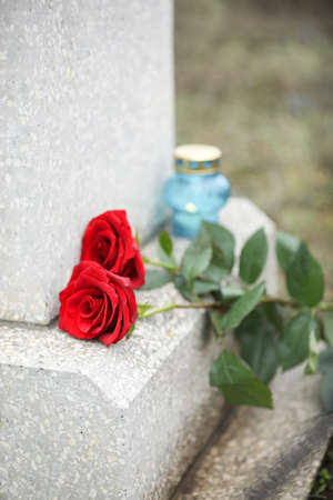 Red roses on old grey tombstone outdoors. Funeral ceremony 스톡 콘텐츠