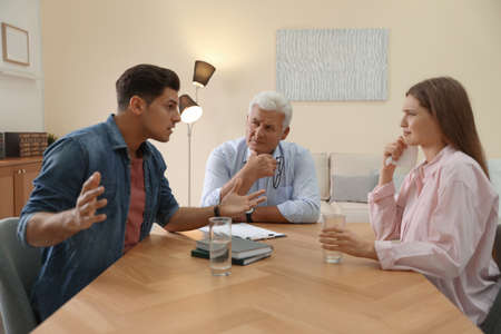 Professional psychotherapist working with emotional couple in office