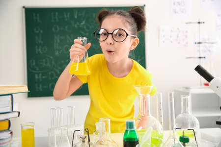Schoolchild making experiment at table in chemistry class