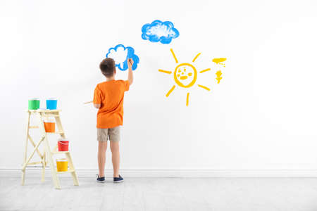 Little child painting cloud on white wall in room