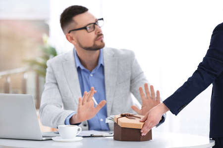 Businessman refusing to take bribe at table indoors