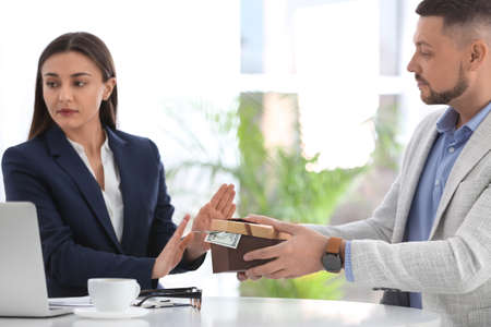 Businesswoman refusing to take bribe at table indoors