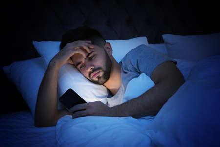 Young man addicted to smartphone in bed at night