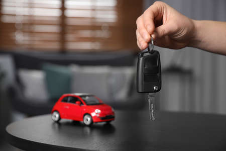 Man holding key near table with miniature automobile model indoors, closeup. Car buying