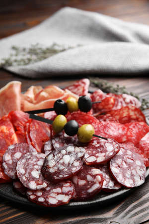 Tasty salami and other delicacies on wooden table, closeup