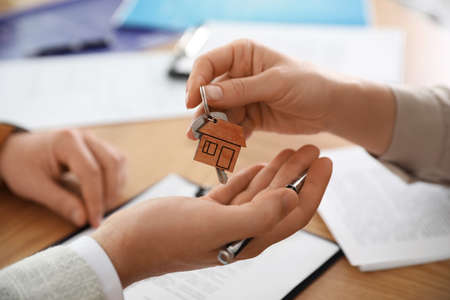 Real estate agent giving key with trinket to client in office, closeup Stock fotó - 140237342
