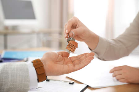 Real estate agent giving key with trinket to client in office, closeup Stock fotó - 140237343