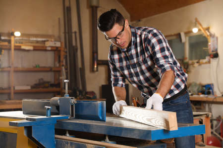 Professional carpenter working with wooden plank in workshop