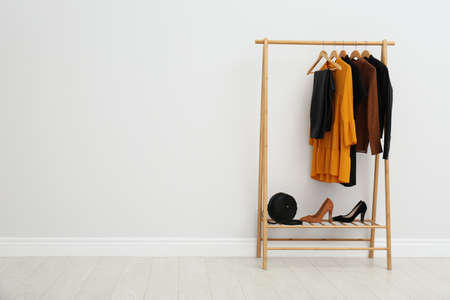 Wooden rack with stylish clothes in room. Space for text