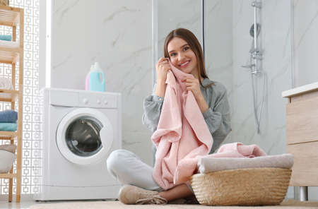 Happy woman with clean towel near washing machine in bathroom. Laundry day