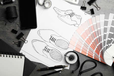 Flat lay composition with drawing of shoes on grey table. Designer's workplace