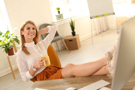 Young woman with cup of drink relaxing at table in office during break Zdjęcie Seryjne