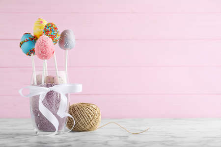 Delicious sweet cake pops on marble table, space for text. Easter holiday