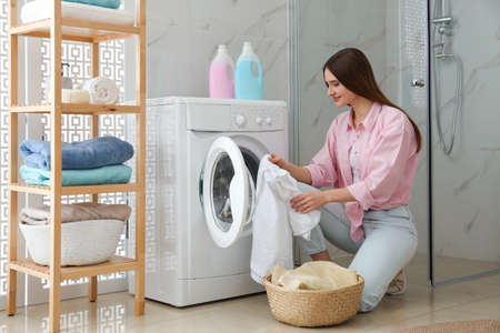 Young woman with clothes near washing machine in bathroom. Laundry day Reklamní fotografie