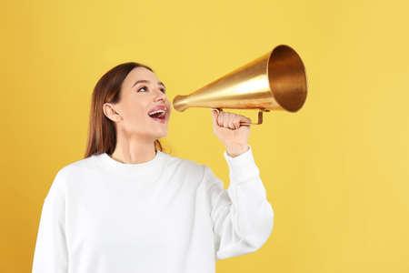 Mujer joven con megáfono vintage sobre fondo amarillo