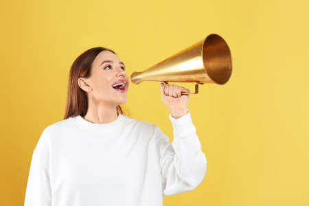 Young woman with vintage megaphone on yellow background