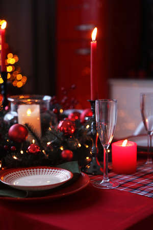 Table served for festive dinner and Christmas tree in stylish kitchen interior