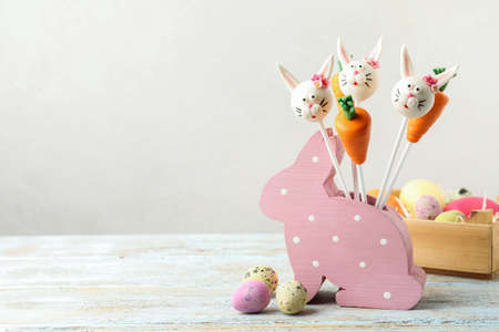Delicious sweet cake pops on white wooden table, space for text. Easter holiday