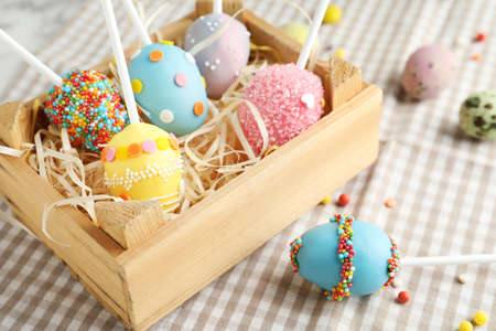 Delicious sweet cake pops in wooden crate on table, closeup. Easter holiday