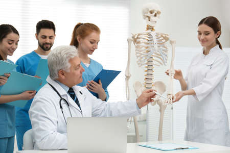 Professional orthopedist teaching medical students in clinic