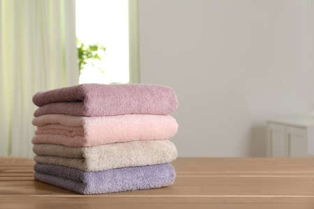 Stack of fresh towels on wooden table in bathroom. Space for text