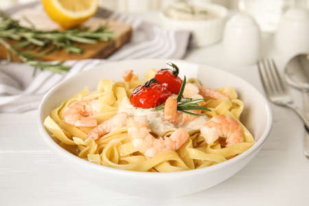 Delicious pasta with shrimps on white wooden table