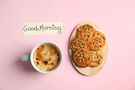 Delicious coffee, cookies and card with words GOOD MORNING on pink background, flat lay