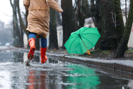 Woman in rubber boots running after umbrella outdoors on rainy day, closeup Stock fotó